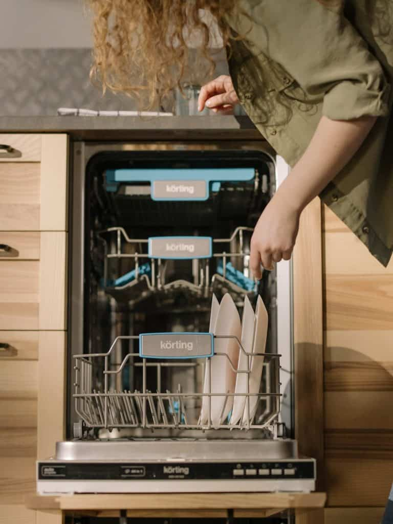 woman sorting plates, looking at the dishwasher, How much does a dishwasher repair cost in Australia