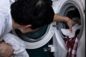 man getting the clothes out from dryer, a malfunctioning heat pump or resistance automatically means partial drying