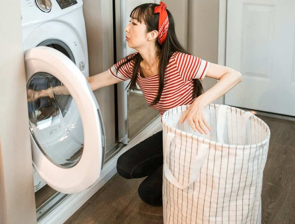 woman getting the clothes inside the dryer, noisy dryer