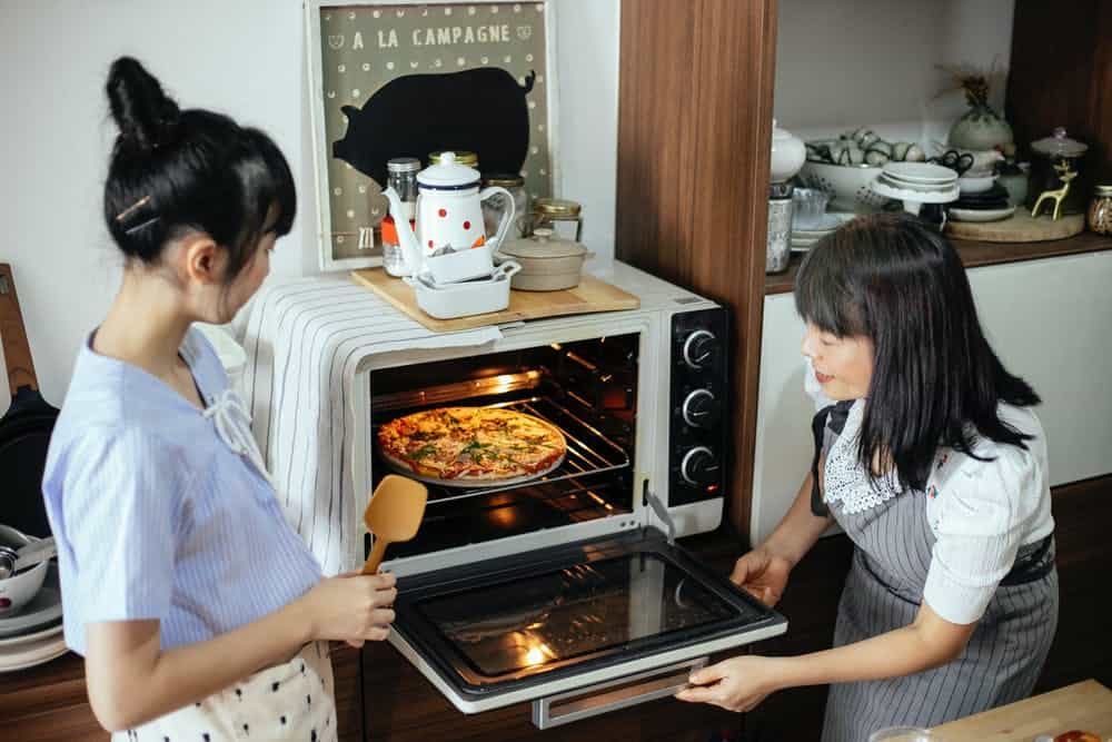 mother and daughter baking pizza in the oven.