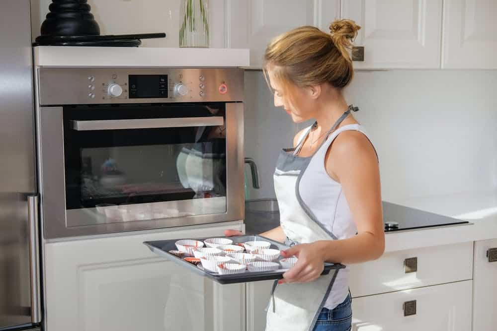 woman trying to bake and looking at the oven.