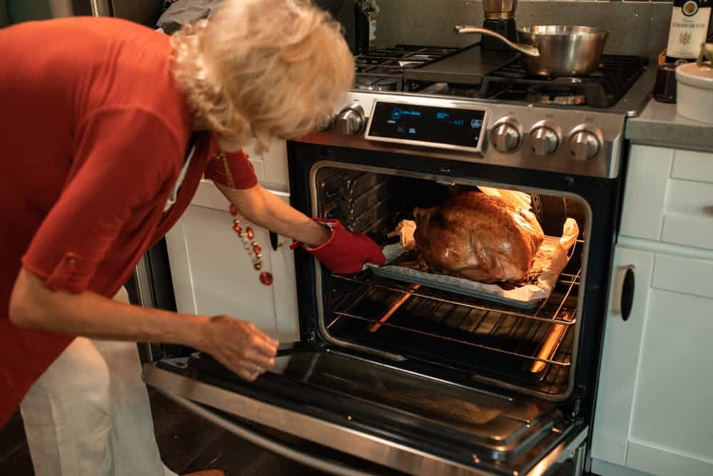 woman roasting chicken in the oven with red gloves.