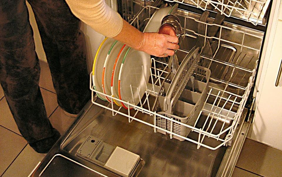 open dishwasher appliance, woman removing plates and glass inside dishwasher to unclog