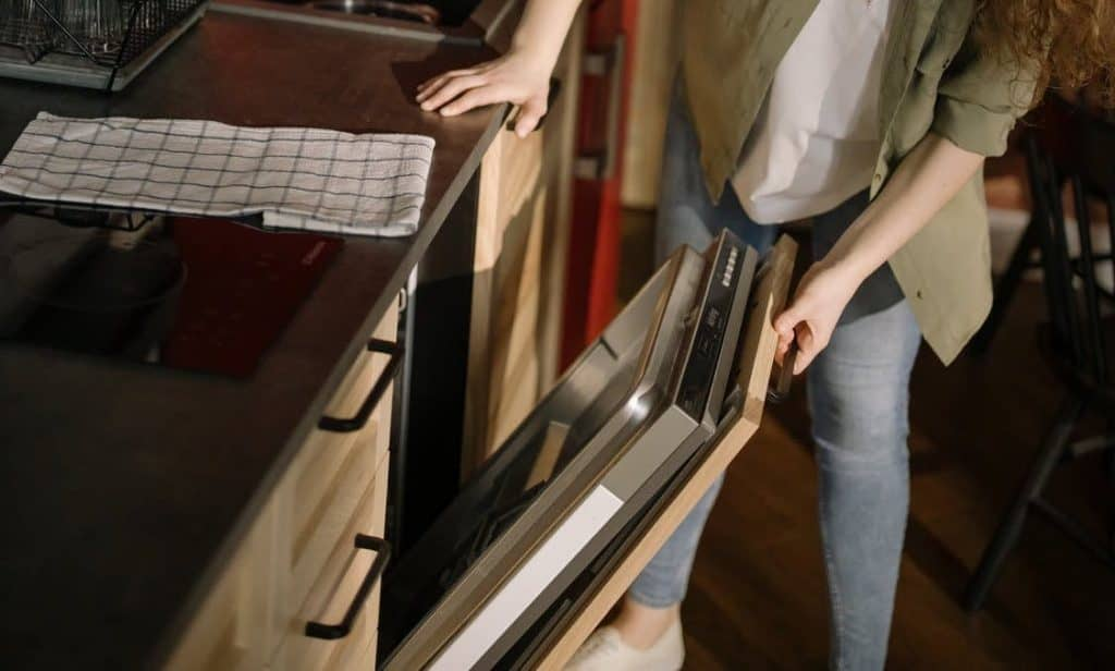 A woman holding the dishwasher door, trying to locate the screws to remove the panel
