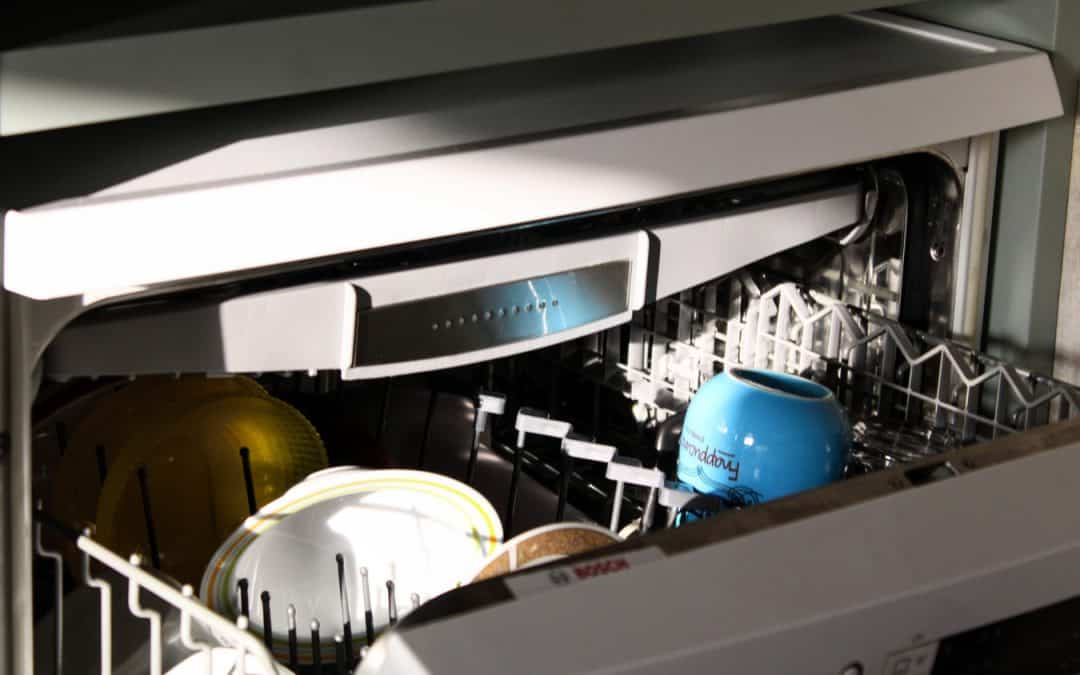 image shows dishwasher with white plates and blue cup or mug