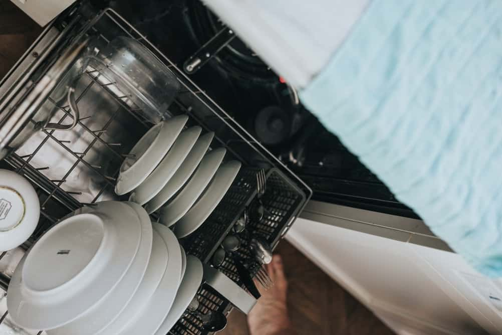dishwasher with plates, saucer and other kitchen wear.