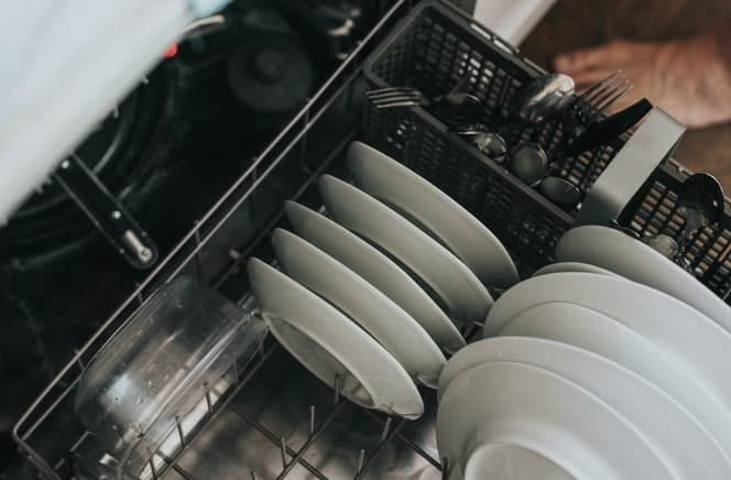 plumbing a dishwasher, white plates and saucer
