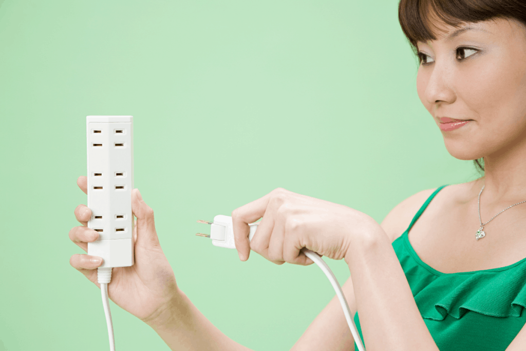 A woman wearing green dress, trying to plug the washing machine on the extension cord